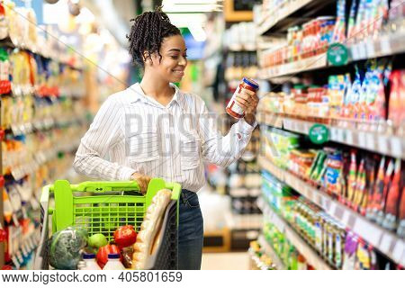 Happy Black Woman Buyer Doing Groceries Shopping Choosing Food And Buying Products Standing With Sho