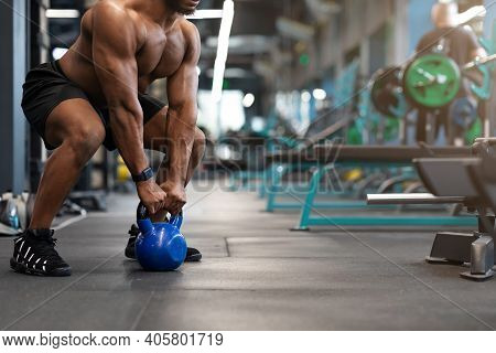 Cropped Of Black Muscular Man Hands Lifting Kettlebell In Empty Gym. Unrecognizable African American