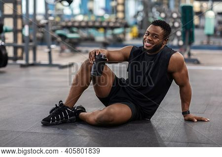 Happy African American Bodybuilder Holding Mug With Water Or Sports Drink, Sitting On Floor At Gym,