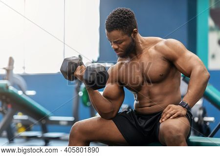 Handsome African American Muscular Shirtless Man Bodybuilder Exercising With Barbell At Gym, Sitting