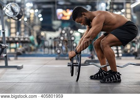 Powerlifting Concept. Side View Of Black Muscular Shirtless Man Pumping Iron In Gym. Athletic Africa