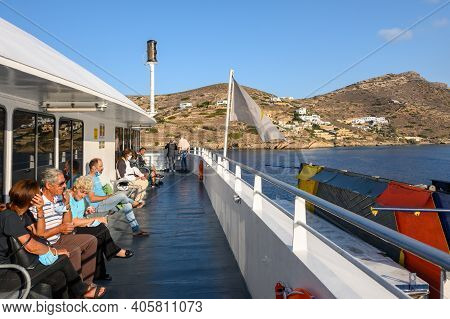 Ios, Greece - September 23, 2020: Tourist Sitting On Bench Of Ferry. Coast Of Ios Island In Backgrou