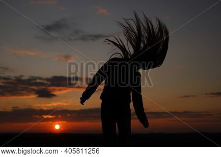 The Girl With Her Hair Down Shakes Her Head. A Silhouette Of A Girl Waving Her Loose Hair During The