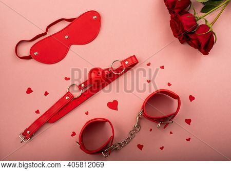 Bdsm Set Of Red Color And A Bouquet Of Roses On A Pink Background. Love Symbol For Valentines Day.