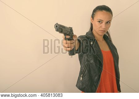 Studio Shot Of Young Asian Woman Aiming Handgun At Distance Against White Background