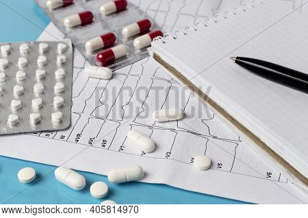 Treatment Of Heart Disease. Myocardial. Stroke. Heart Cardiogram, Doctors Notebook And Pills On A Bl