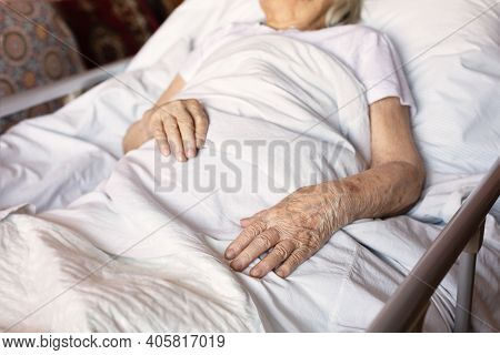 Hands Of Elderly Sick Woman Lying On Her Bed At Home. Concept: Age, Social Help Lonely, Health Care