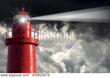 Closeup Of An Old Red Lighthouse With Storm Clouds On The Background, Bad Weather.