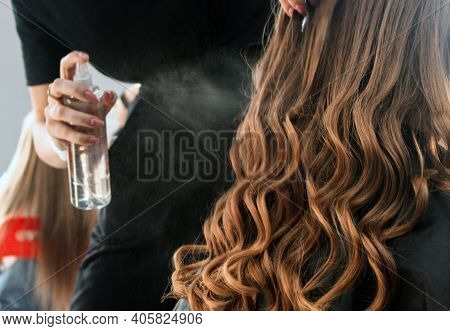 Hairdresser Fixing A Coiffure With Ringlets Of A Young Girl Using A Hair Spray In A Beauty Salon. Co