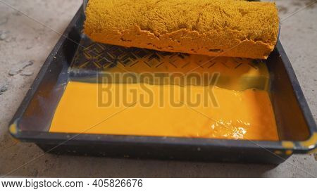 A Man Pours Yellow Paint Into A Tray. Yellow Paint Slowly Pours Into Black Paint Tray. Wall Painting