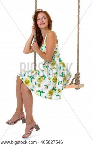 Beautiful Young Woman Swinging On Rope Swing. Side View Of Happy Woman Wearing Summer Dress Sitting