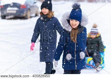 children plays and sleigh rides in winter outdoor, they having fun on snowy winter