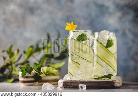 Cucumber Infused Detox Water With Mint In A Glass With Ice. Homemade Flavored Lemonade On Light Blue