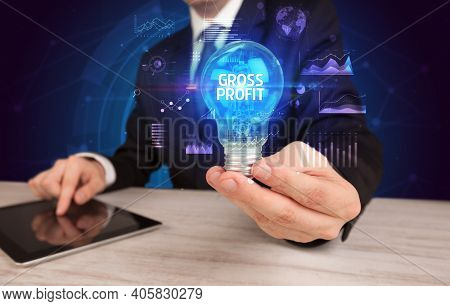 Businessman holding lightbulb with GROSS PROFIT inscription, Business idea concept