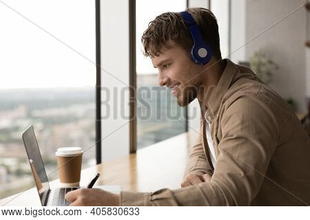 Young Male Translator In Headphones Engaged In Video Remote Interpreting