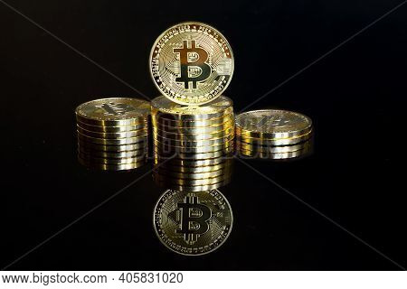 Golden Bitcoins Stacked As A Winner Podium. Isolated On A Black Background With Reflection