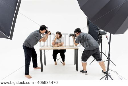 Asian Photographer 2 Men Taking Photos Of Portrait Female Model Who Is Fat And Eating Pizza, At A Ph