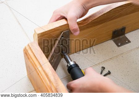 A Little Boy Unscrews The Wooden Table With A Screwdriver