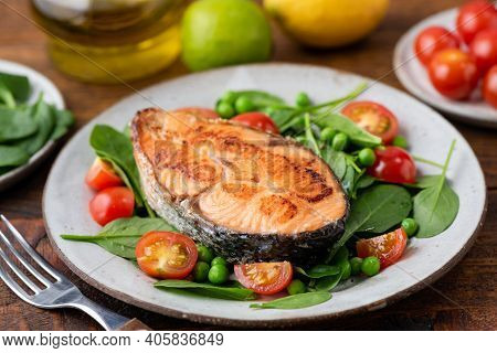Roasted Salmon Steak With Baby Spinach And Cherry Tomatoes On A Plate. Healthy Meal