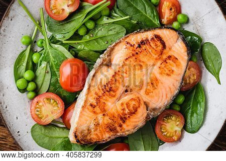 Roasted Salmon Steak Served With Greens And Cherry Tomatoes. Healthy Dinner Or Lunch Meal