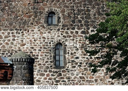Old Stone Wall With Small Windows And A Turret.