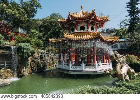 Golden Dragon Water Fountain Statue With Pond And Buddhist Gazebo In Taipei Taiwan.
