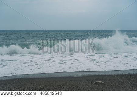 Lone Crashing Wave On Black Rocky Beachfront.