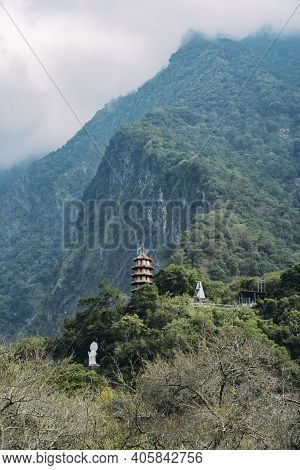 Wide View Of Xiangde Temple From Valley Below With Sharp Cliffs Behind.
