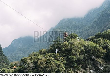 Landscape View Of Xiangde Temple From Valley Below With Sharp Cliffs Behind And Misty Sky.