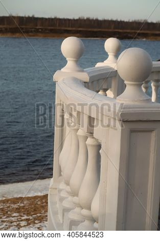 Blue Water Surface, Sandy Shore And Balusters Of The Observation Deck Against The Background Of The