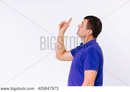 Sign Language. Caaucasian Man Wearing Casual Clothes Looks Up And Points Up With Index Finger Agains