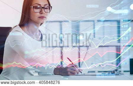 Business Woman Writing Down Some Figures Based On Stock Market Rates To Predict Behaviour Of Forex C