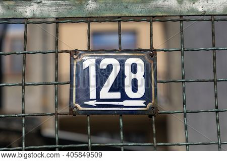 Number 128, The Number Of Houses, Apartments, Streets. The White Number On A Blue Metal Plate, House
