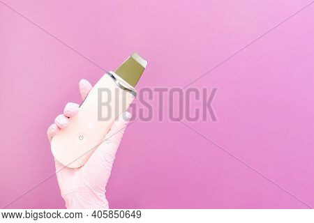 Cosmetology Concept, Cosmetologist In Hand Are Ultrasonic, Pink Background. Ultrasonic Face Cleaner