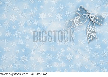 Blue Bow With White Snowflake On Blue Snowflake Textured Material Background With Copy Space For You