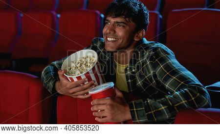 Portrait Of Cheerful Young Guy Smiling, Holding A Drink And Popcorn Basket While Watching Movie Alon