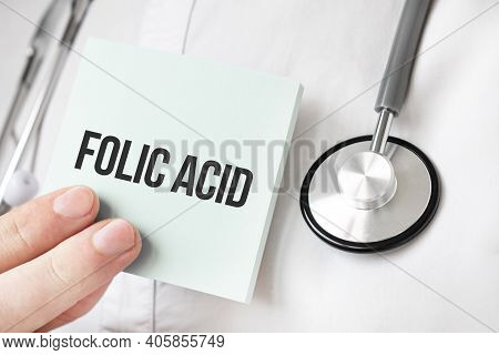 Doctor Holding Card In Hands And Pointing The Word Folic Acid