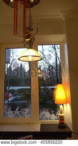 Window With Christmas Patterns On The Glass And A Lamp On The Windowsill