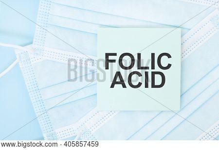 Piece Of Paper With Phrase Folic Acid On Pile Of Blue Medical Masks. Coronavirus Pandemic Concept