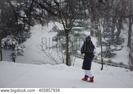 Girl With A Child In Her Arms Are Walking In A Winter Park. Young Woman Wearing A Black Jacket And K