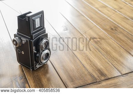 Close-up Of An Antique Twin Lens Reflex Camera, On A Wooden Table, With Copy Space, Vintage And Anti