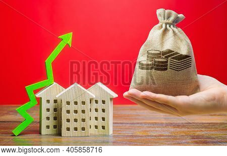 Money Bag And Wooden Houses With An Arrow Up. Real Estate Concept. Business And Finance. Savings On