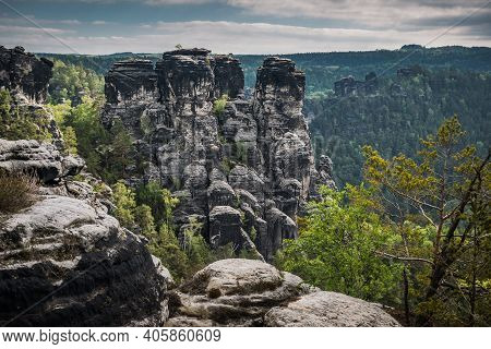 Trekking path in Bastei sandstone mountains leading to Bastei bridge. Forest with large old trees, s