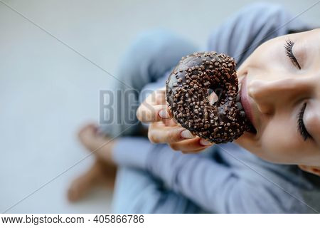 Portrait Of Rejoicing Woman Eats Tasty Donut At Home.