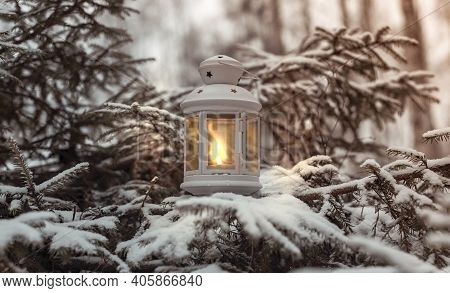 Glowing Candle In Lantern Hanging On Fir Tree Branch In Winter Forest. Christmas Scene.