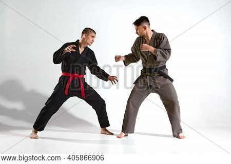 Athletic Males In Kimono Fighting During Kudo Workout On White Studio Background With Copy Space, Ma