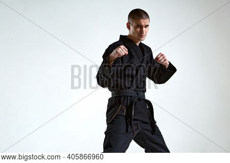 Confident Man In Black Kimono Fighter Posing In Karate Stance On White Studio Background With Copy S