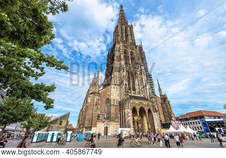 Ulm, Germany - July 20, 2019: People Walk Next To Ulm Minster Or Cathedral Of Ulm City. This Medieva