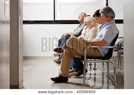 Row of multiethnic people sitting side by side while waiting for doctor in hospital lobby