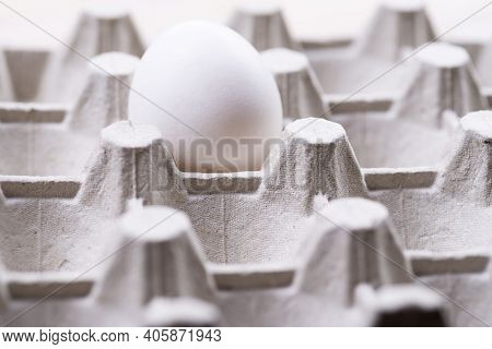 Raw Egg Carton Box With One Egg Close-up. Gray Egg Carton. Waste Paper Container For Packing Raw Egg